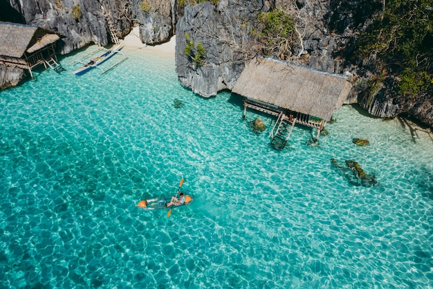 Człowiek kajakarstwo w bliźniaczej lagunie między skałami i domami rybaków, ciesząc się krajobrazem. pojęcie o podróżach na filipinach