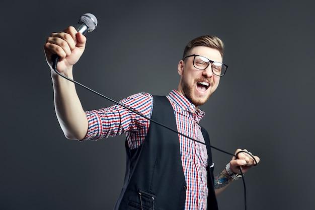 Człowiek karaoke śpiewa piosenkę do mikrofonu, piosenkarz