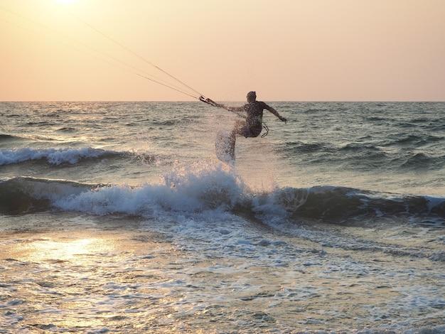 Człowiek kitesurfing w pobliżu wybrzeża o zachodzie słońca