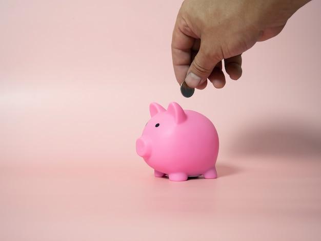 Człowiek kładzie monetę w skarbonce na różowym tle, zbliżenie. miejsce na tekst