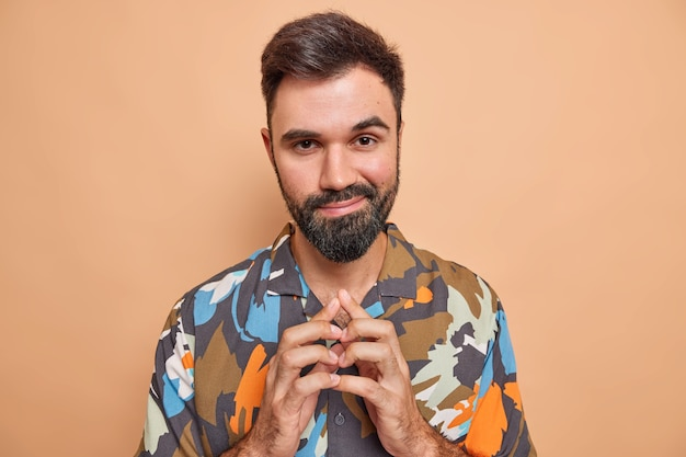 Człowiek knuje coś krępuje palce ma przebiegły wyraz zły plan myśli o czymś przebiegły nosi kolorową casualową koszulę na białym tle na beżowym studio