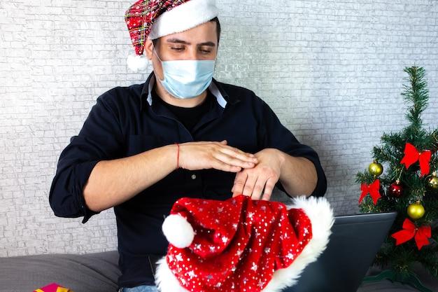 Człowiek komunikuje się za pomocą języka migowego. facet w santa hat obok laptopa prowadzi interakcję poprzez wideorozmowy. żyj z niepełnosprawnością. boże narodzenie w odosobnieniu w domu. dystans społeczny na wakacje.
