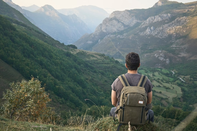 Człowiek kontempluje ścieżkę biegnącą przez dolinę między górami w pochmurny dzień z plecakiem za sobą