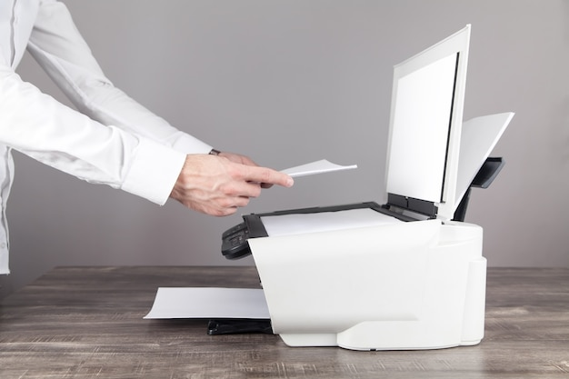 Człowiek kopiowanie i skanowanie dokumentów w biurze.