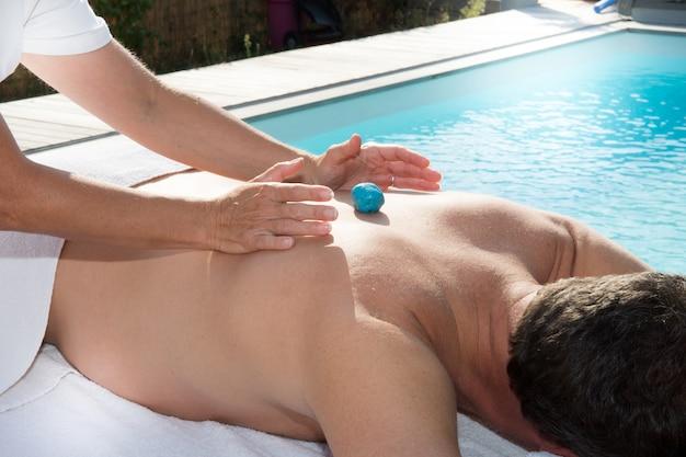 Człowiek korzystający z masażu gorącymi kamieniami przy basenie