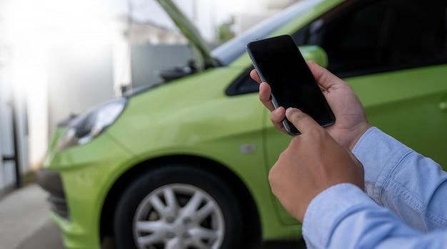 Człowiek korzystanie z telefonu komórkowego w celu pomocy pomoc w zepsutym samochodzie pomaga zatrzymać awarię samochodu