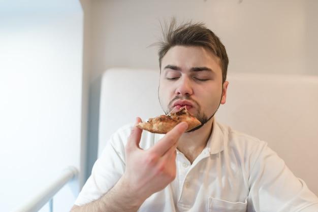 Człowiek, który je kawałek pizzy na jasnym tle. mężczyzna w bieli czerpie przyjemność z jedzenia pizzy.