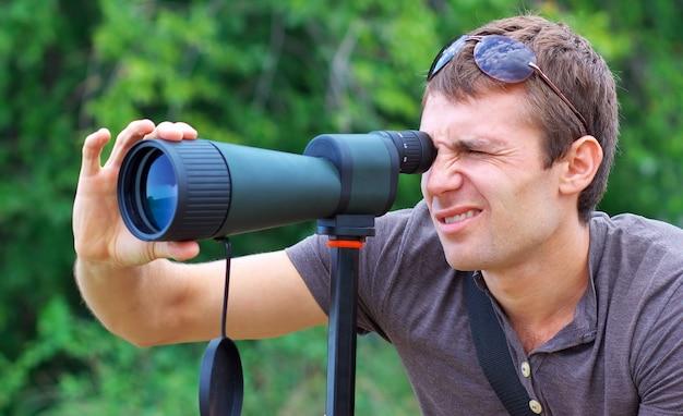 Człowiek, który obserwuje w lunecie. pozytywny człowiek patrzący przez teleskop