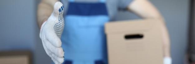 Człowiek ładujący z pudełkiem stoi wyciągając rękę. firma zajmuje się wszystkimi etapami transportu mebli we własnym zakresie. umów się na przeprowadzkę biura. wyrzuć niepotrzebne śmieci. opakowania mebli biurowych