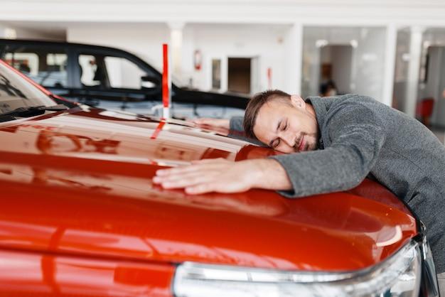 Człowiek leżący na masce nowego samochodu w salonie.