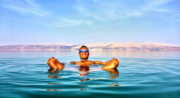 Człowiek leży w martwym morzu. jordania na tle. izrael