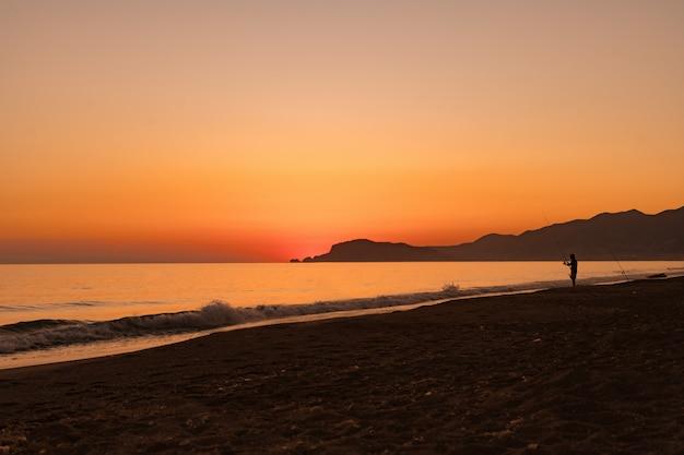 Człowiek, łowienie ryb w morzu na wschód słońca
