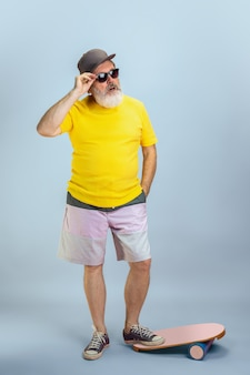 Człowiek łyżwiarz. portret mężczyzny starszy hipster w okulary na białym tle na jasnoniebieskim tle studio. koncepcja tech i radosny starszy styl życia. modne kolory, wieczna młodość. miejsce na reklamę.
