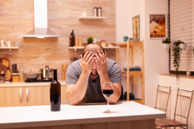 Człowiek mający problemy z alkoholem podczas kryzysu życiowego z butelką wina w kuchni siedzi przy stole. choroba nieszczęśliwa i lęk, uczucie wyczerpania z powodu problemów z alkoholizmem.