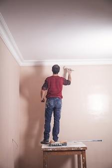 Człowiek malowanie ścian pędzlem. renowacja