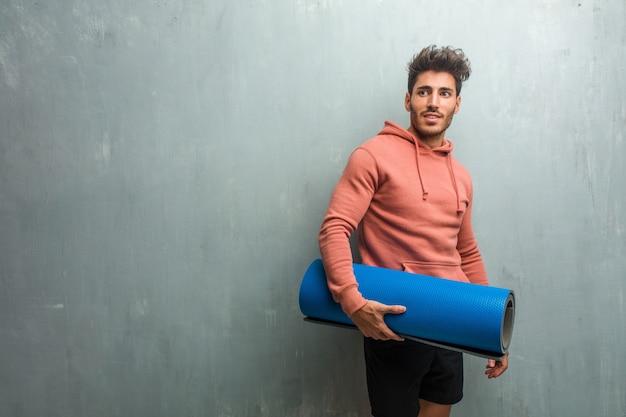 Człowiek młody fitness na ścianie grunge przekraczania ramion, uśmiechnięty i szczęśliwy, będąc pewny siebie i przyjazny.