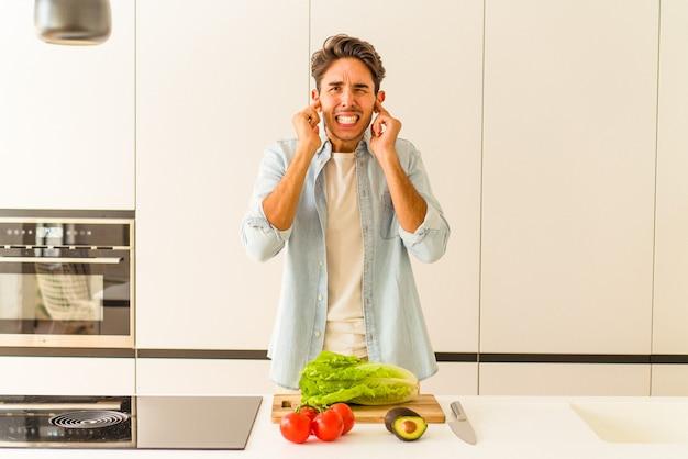 Człowiek młody rasy mieszanej przygotowuje sałatkę na lunch, zakrywając uszy rękami.