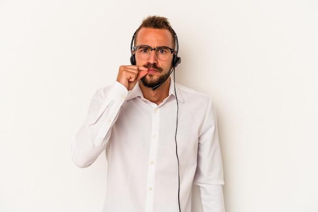 Człowiek młody telemarketer kaukaski z tatuażami na białym tle z palcami na ustach zachowując tajemnicę.