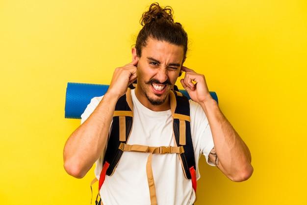 Człowiek młody turysta kaukaski z długimi włosami na białym tle na żółtym tle obejmujące uszy rękami.