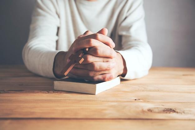 Człowiek modlący się przed biblią