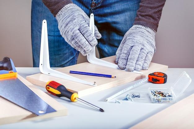 """Człowiek montujący meble za pomocą narzędzi ręcznych. projekt """"zrób to sam""""."""