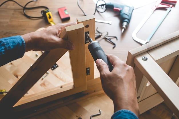 Człowiek montuje drewniane meble, naprawia lub naprawia dom za pomocą śrubokręta