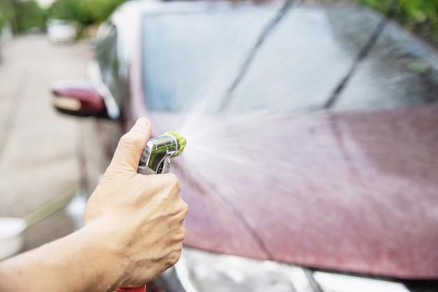 Człowiek mycie samochodu za pomocą szamponu i wody