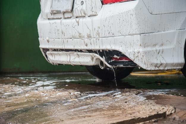 Człowiek myje samochód ręcznie za pomocą preparatu piankowego do polerowania