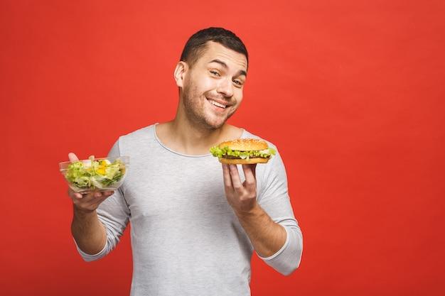 Człowiek myśli wybierając między sałatką a hamburgerem, zdrowym i niezdrowym jedzeniem.