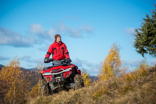Człowiek na czerwonym quadzie atv przeciw błękitne niebo