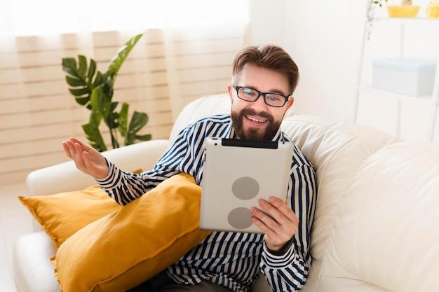 Człowiek na kanapie w domu z tabletem