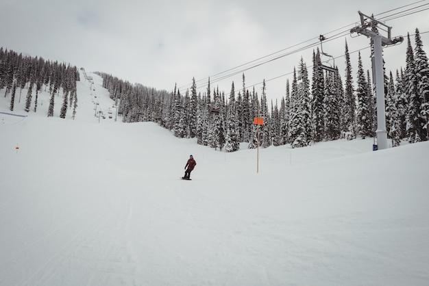 Człowiek na nartach na zaśnieżonych alpach w ośrodku narciarskim