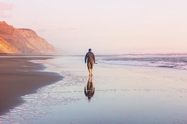 Człowiek na plaży oceanu o zachodzie słońca. koncepcja wakacji.