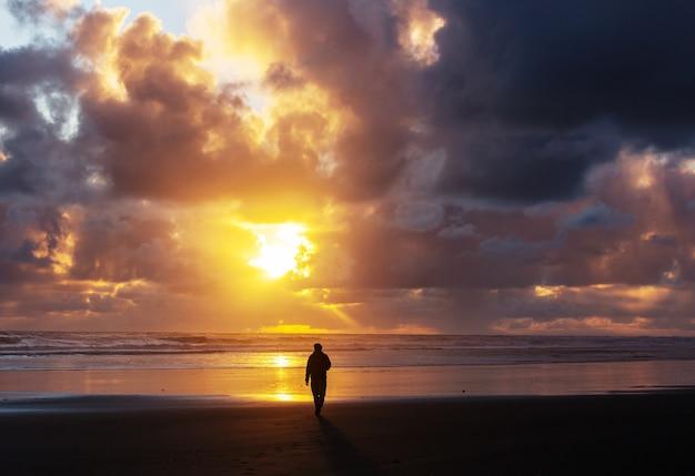 Człowiek na plaży oceanu o zachodzie słońca. tło wakacje koncepcja.