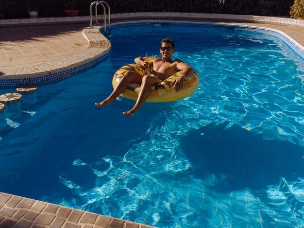 Człowiek na pływający pierścień w basenie domu willi
