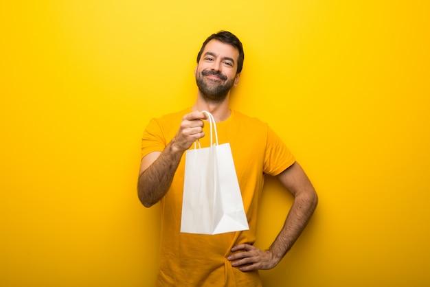 Człowiek na pojedyncze żywe żółty kolor trzyma wiele toreb na zakupy