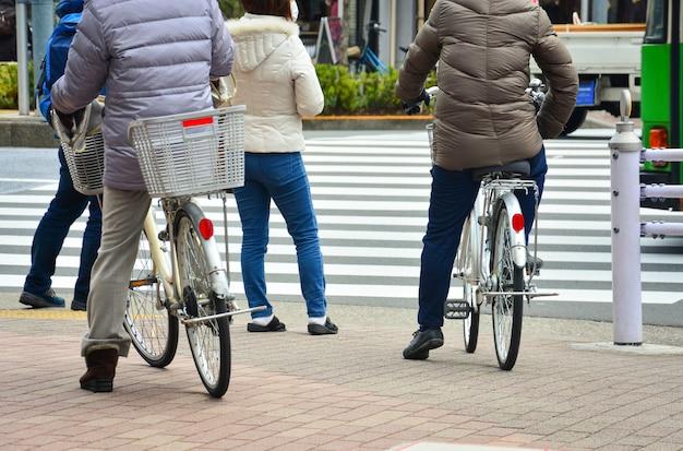 Człowiek na rowerze i pieszych na skrzyżowaniu czekają, aby przejść przez drogę na krzyżu zebry