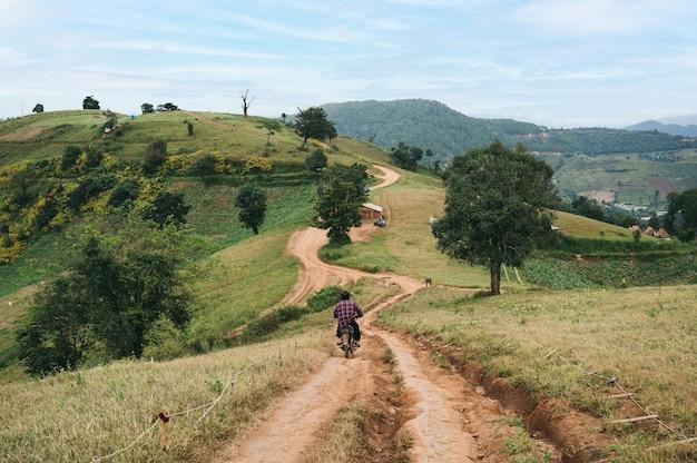 Człowiek na rowerze stary motocykl na żwirowej drodze w dół do zielonego wzgórza na wsi