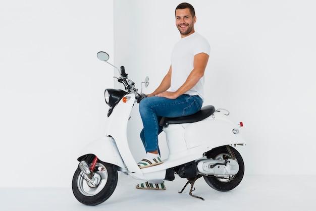 Człowiek na skuter jest szczęśliwy i patrząc na kamery