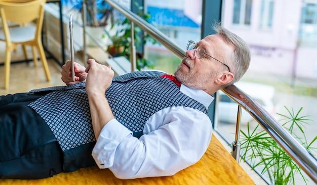 Człowiek na stole z tabletem. wideokonferencja w izolacji. pojęcie biznesu, praca przy komputerze, praca na odległość. zostań w domu, aby być zdrowym.