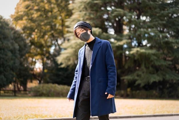 Człowiek na świeżym powietrzu w parku z maską