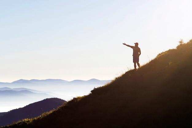 Człowiek na szczycie góry. scena emocjonalna. młody człowiek z plecakiem stojący z uniesionymi rękami na szczycie góry i podziwiając widok na góry. turysta na szczycie góry. koncepcja sportu i aktywnego życia.
