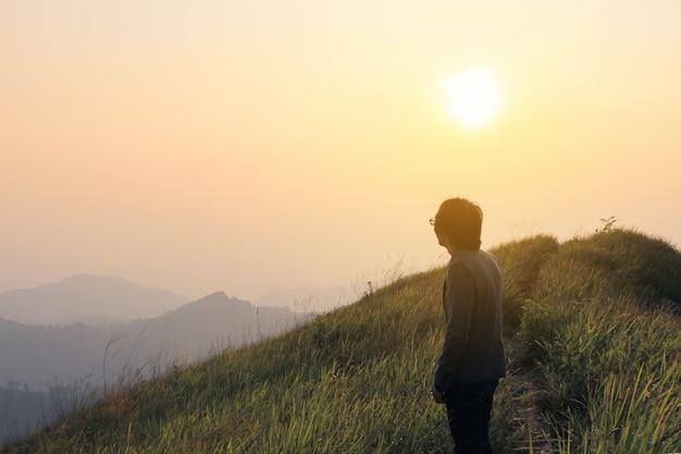 Człowiek na szczycie wzgórza oglądania wspaniałych krajobrazów w górach podczas lata kolorowych w tajlandii. vintage filtrowany obraz.