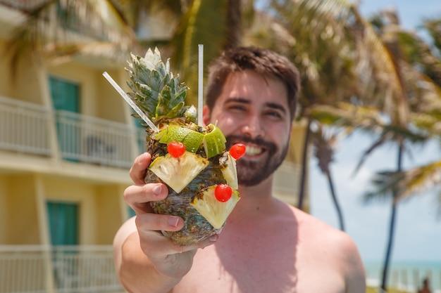 Człowiek na wakacjach w risort picie słodkiego ananasa.