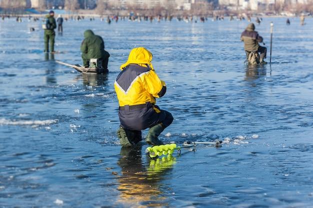 Człowiek na zimowym wędkowaniu, ludzie na lodzie zamarzniętego jeziora, rybacy, miejski krajobraz,