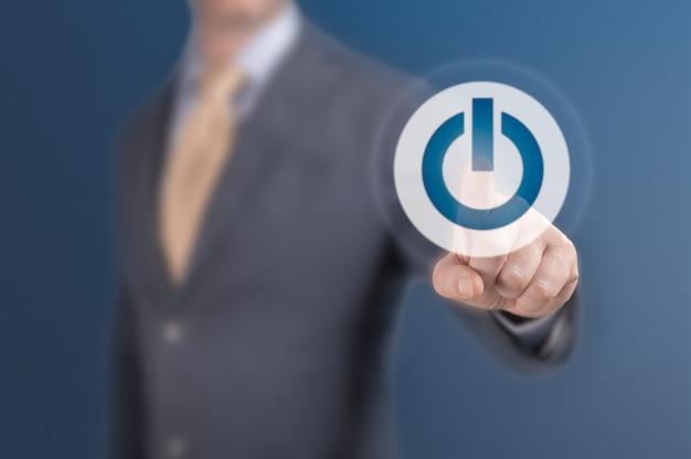 Człowiek naciśnij start. biznesmen naciskając przycisk zasilania koncepcja. biznesmen naciskając proste przyciski start na wirtualnym tle. koncepcja biznesowa, technologiczna, internetowa i sieciowa