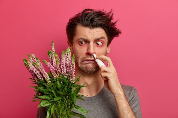 Człowiek nadwrażliwy ma katar sienny, jego układ odpornościowy reaguje na obcą substancję, ma opuchnięte zaczerwienione oczy, stosuje krople do nosa w celu skutecznego leczenia, stoi w pomieszczeniach. koncepcja sezonowej alergii i nieżytu nosa