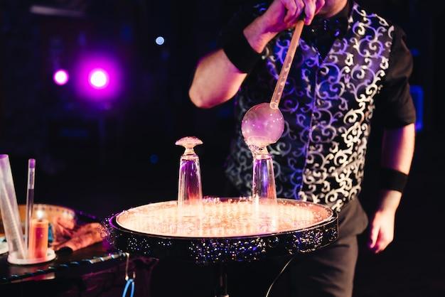Człowiek napełnia bańkę mydlaną. duża bańka mydlana.