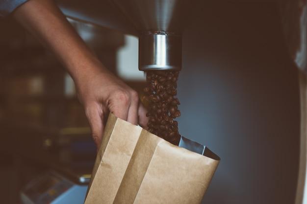 Człowiek napełniania pakietu ziaren kawy
