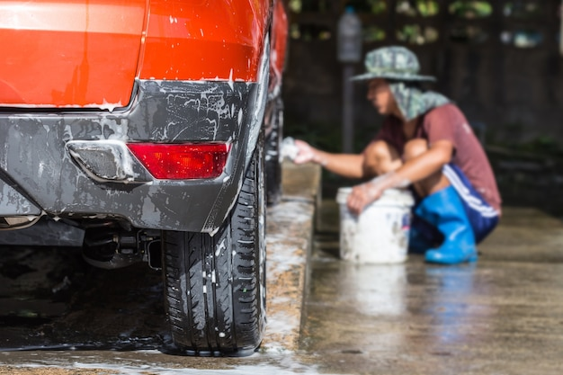 Człowiek natrysku myjki ciśnieniowej do myjni samochodowej w sklepie pielęgnacji samochodu